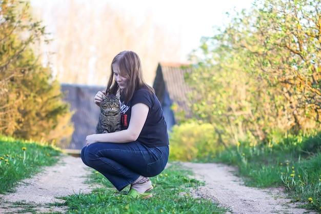 A menina adolescente brincando com seu lindo gato cinza listrado ao ar livre em fundo de natureza primavera na zona rural.