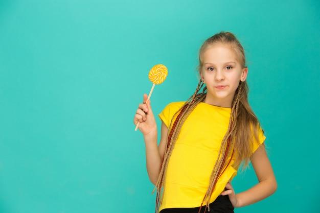 A menina adolescente com pirulito colorido em um azul