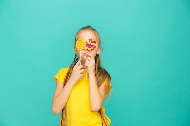A menina adolescente com pirulito colorido em uma parede azul