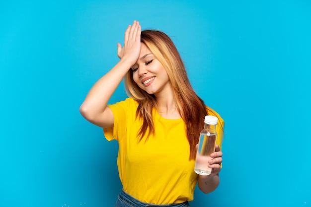 A menina adolescente com uma garrafa de água sobre um fundo azul isolado percebeu algo e pretende a solução