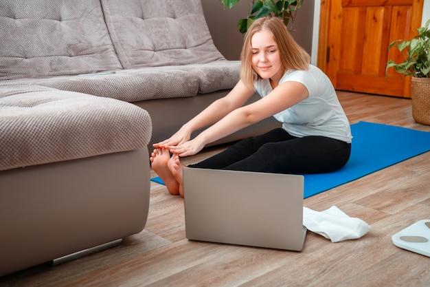 A menina adolescente em roupas esportivas faz aulas de ioga de exercícios de ioga remota sentada em posição de lótus durante a estadia em casa. jovem mulher faz exercícios de fitness na sala de estar usando o laptop via videochamada.