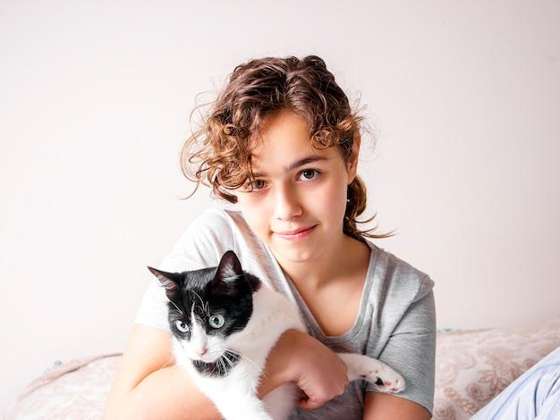 A menina adolescente encaracolado bonita na cama abraça seu gato