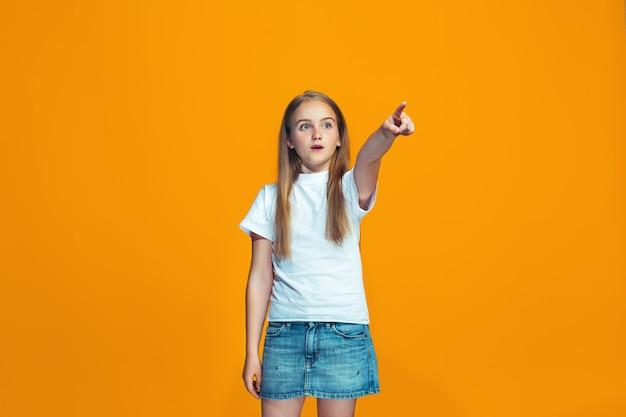 A menina adolescente feliz, apontando para você, meio retrato do close up do comprimento no espaço alaranjado.