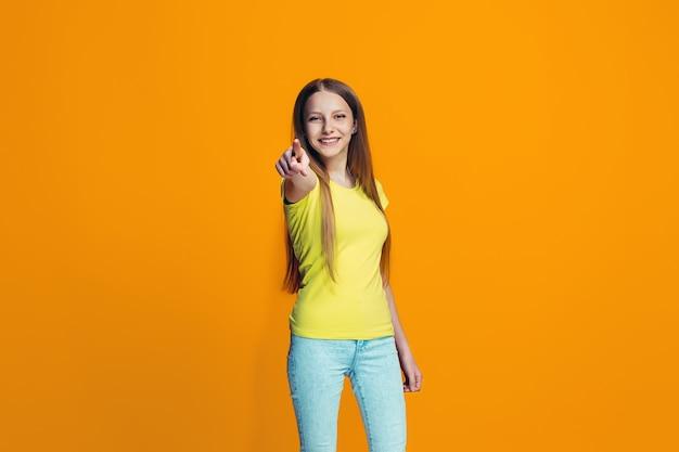 A menina adolescente feliz, apontando para você, retrato de meio comprimento closeup