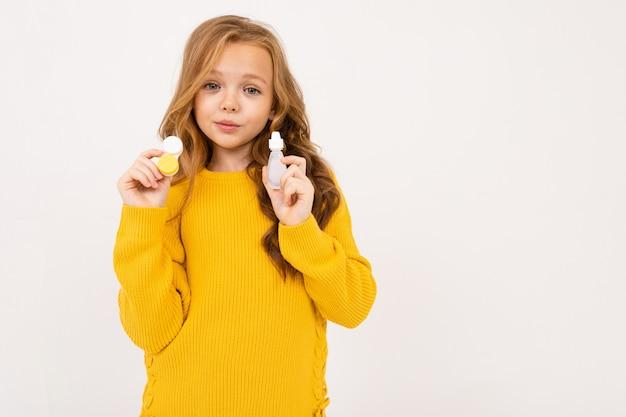 A menina adolescente feliz com cabelo vermelho, calças com capuz e amarelo mantém as lentes de contato isoladas no branco