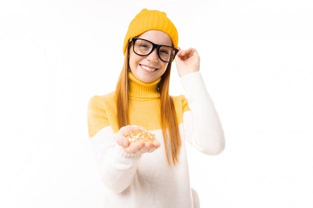 A menina adolescente feliz com cabelo vermelho, hoody e chapéu prende as vitaminas isoladas no fundo branco