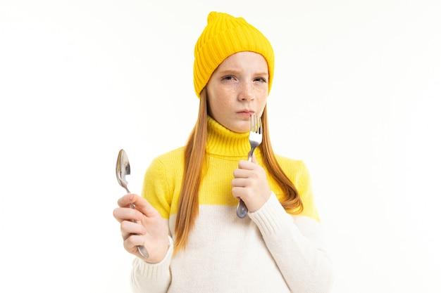 A menina adolescente feliz com cabelo vermelho, hoody e chapéu prende uma colher e um garfo isolado no fundo branco