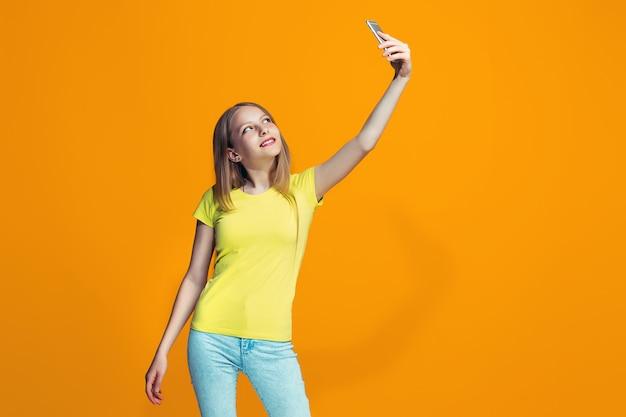 A menina adolescente feliz em pé e sorrindo contra a parede laranja