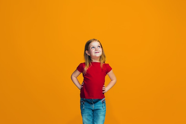 A menina adolescente feliz que está e que sorri contra o fundo alaranjado.
