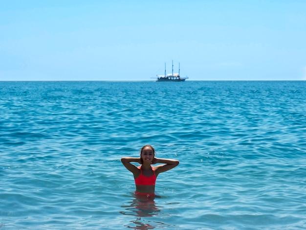 A menina adolescente nova nada e tem o divertimento no mar