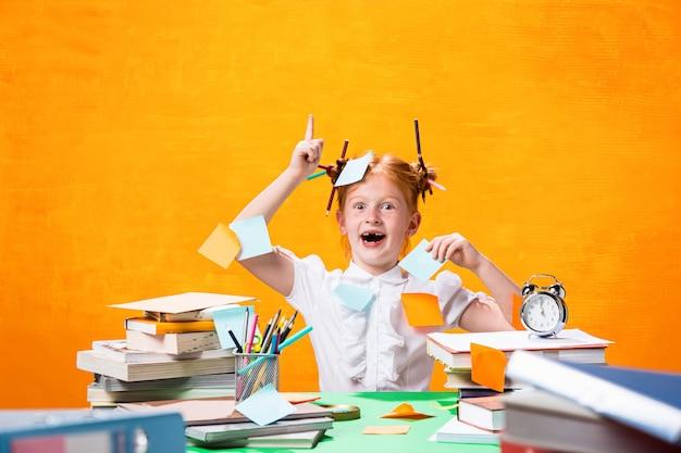 A menina adolescente ruiva com muitos livros em casa. fotografia de estúdio