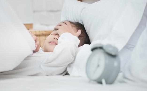 A menina adorável asiática que coloca nos olhos brancos da tampa de cama com a mão preguiçosa para acordar