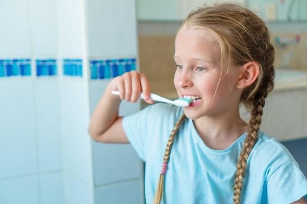 A menina adorável pequena escova os dentes no banheiro.