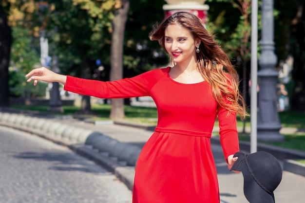A menina adulta sorridente no vestido vermelho está pegando um táxi na rua da cidade.