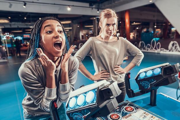 A menina africana e branca está pilotando naves espaciais na arcada.