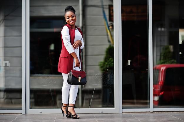 A menina afro-americano com bolsa levantou ao ar livre da cidade dos steets.