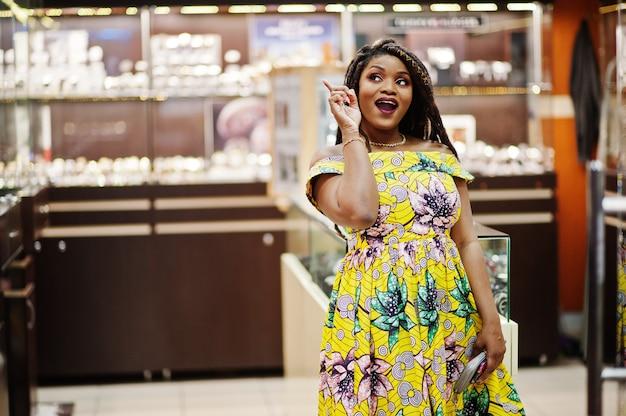 A menina afro-americano da altura pequena bonito com dreadlocks, veste no vestido amarelo colorido, na loja dos relógios no shopping.