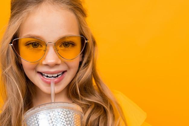 A menina agradável com seus óculos bebe um cocktail e sorri na parede branca
