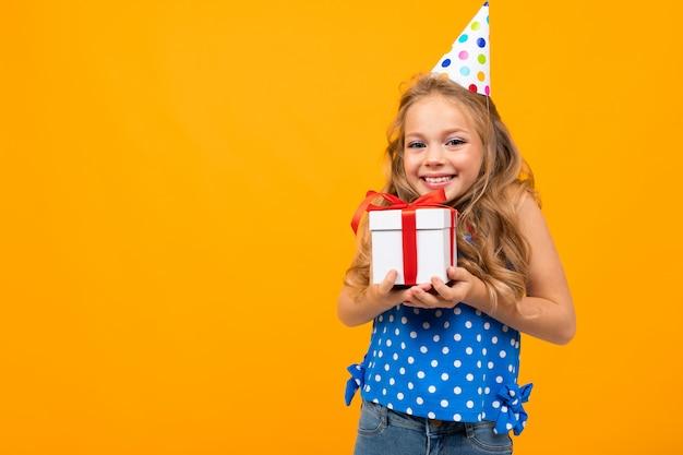 A menina agradável com uma festa de aniversário mantém um presente isolado no branco