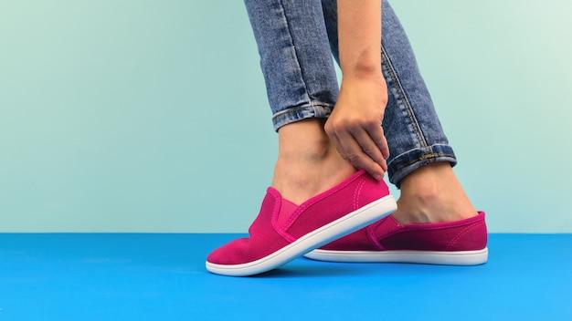 A menina ajeita os sapatos vermelhos no chão azul
