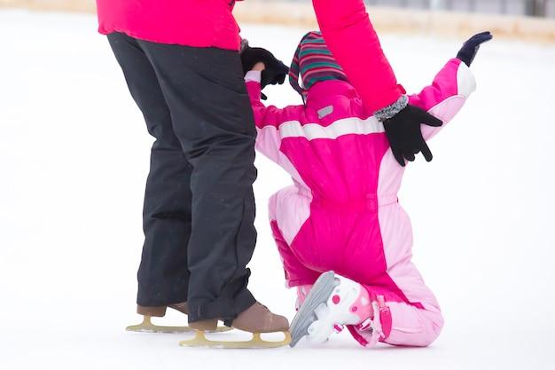 A menina ajuda a criança a patinar no gelo