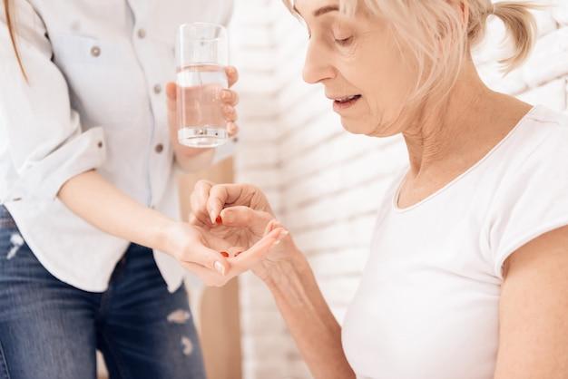 A menina ajuda a mulher adulta a beber comprimidos.