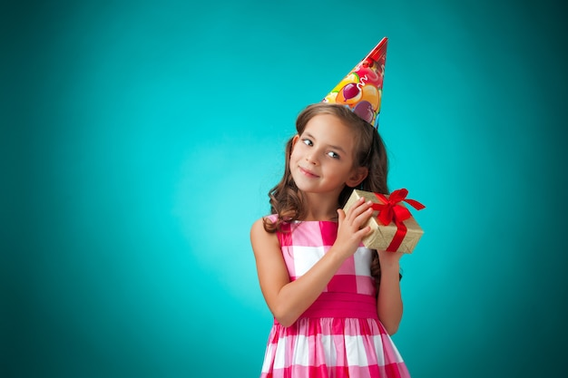 A menina alegre bonitinha com chapéu de festa na parede azul