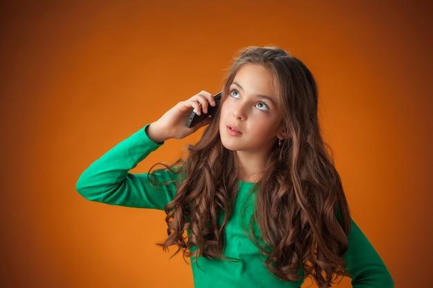 A menina alegre bonitinha com smartphone na parede laranja