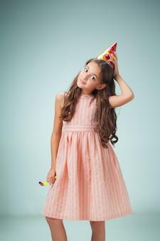 A menina alegre bonitinha com tampa festiva na parede cinza