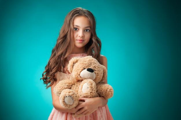 A menina alegre bonitinha com urso de pelúcia na parede azul