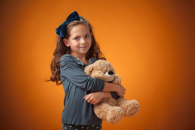 A menina alegre bonitinha em fundo laranja