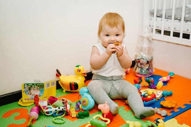 A menina alegre comendo bagel, mostra e brinca muitos brinquedos em tapete colorido e quebra-cabeças