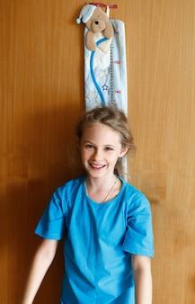 A menina alegre de 8 anos mede o crescimento no fundo de textura da parede de madeira.
