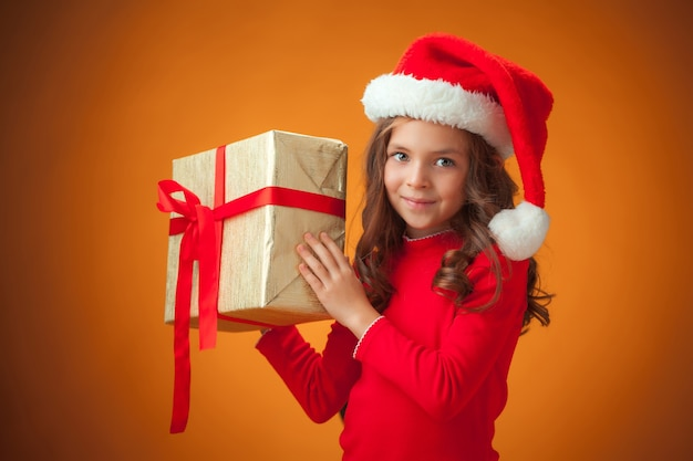 A menina alegre e bonita com chapéu de papai noel e presente em fundo laranja