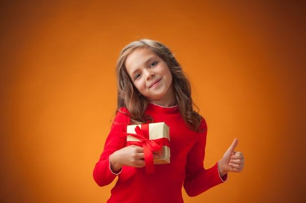 A menina alegre e bonita com um presente em fundo laranja