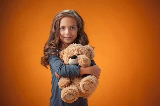 A menina alegre e fofa em fundo laranja