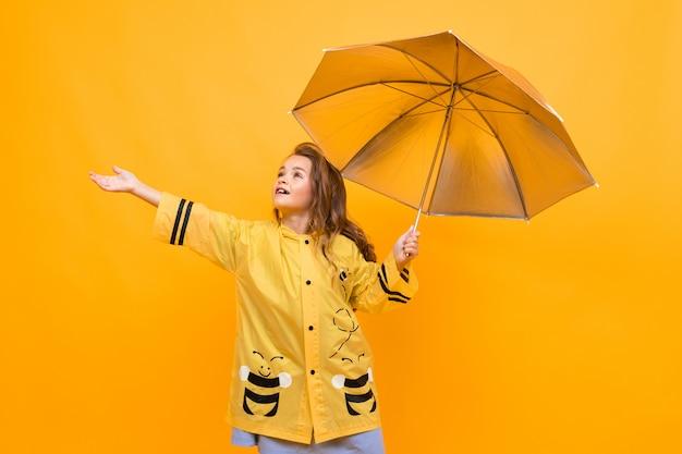 A menina alegre feliz em uma capa de chuva amarela bonita na imagem de uma abelha prende um guarda-chuva de prata e estende a mão em um fundo amarelo