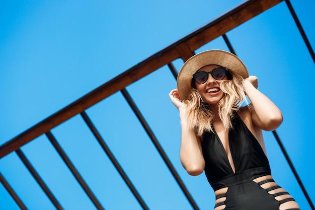 A menina alegre nova bonita no chapéu e nos óculos de sol descansa na praia da manhã