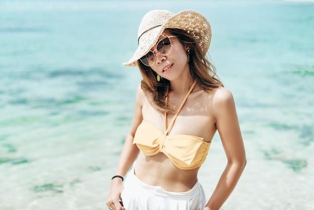 A menina alegre veste o biquini e o chapéu branco que levantam emocionalmente com ondas do mar e horizonte no fundo. mulher bonita em pé de traje de óculos escuros e laranja na praia no fundo do mar azul