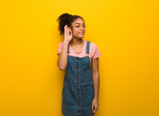 A menina americana africana preta nova com olhos azuis tenta escutar uma bisbilhotice