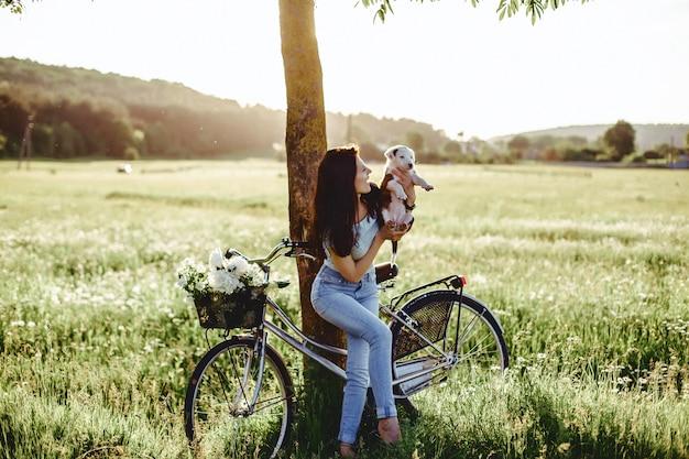 A menina anda com um cachorrinho em um campo em uma bicicleta na parte de trás da luz do sol