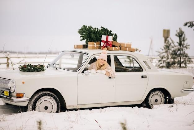 A menina anda em um carro retrô, decorado com uma árvore de natal e apresenta em um bosque nevado. o conceito de uma sessão de fotos de natal no inverno