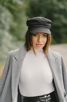 A menina anda. mulher com um casaco cinza. morena com boné preto.