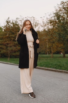 A menina anda. mulher com um casaco preto. senhora lá fora.