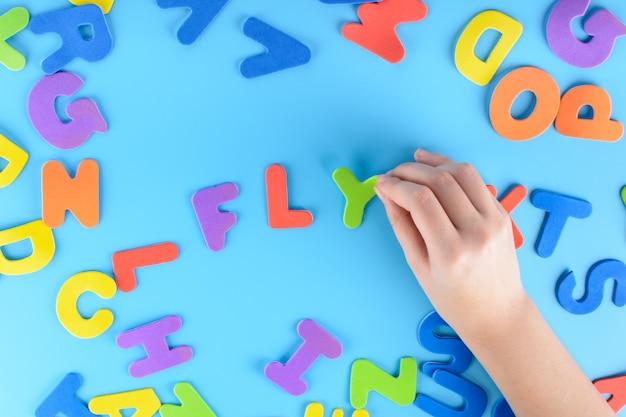 A menina apaga as letras multicoloridas que as palavras voam. fundo bonito.