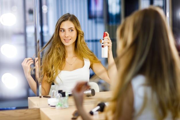 A menina aplica um spray de cabelo para manter o penteado longo