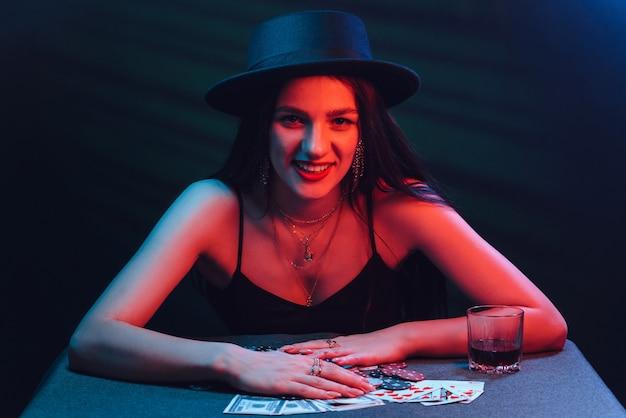 A menina apostadora de chapéu joga pôquer em uma mesa com cartas com luzes vermelhas e fundo escuro
