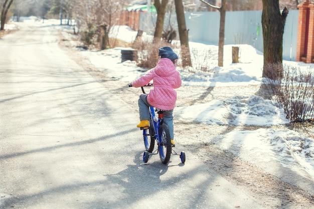 A menina aprende a andar de bicicleta com rodas de segurança na estrada da aldeia quando a neve ainda não derreteu