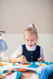 A menina aprende a decorar pão de gengibre com glacê de açúcar