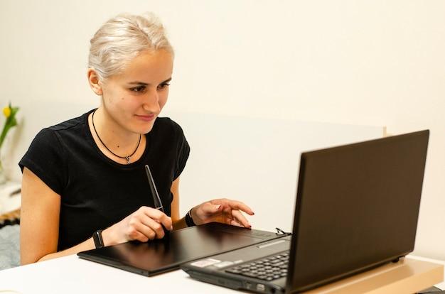 A menina aprende a desenhar em uma mesa digitalizadora. caderno. ensino à distância em casa. freelancer, designer.